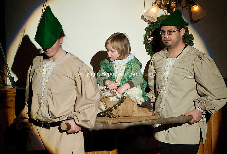 WINSTED, CT-010414JS05- Toby King rides atop the Yule Log as it is carried in by Ashely Jones and Erik Fontanez during the 24th Annual Boar's Head Festival Saturday at the First Church of Winsted. The even continues with a show today (Sunday) at 4 p.m. Tickets are still available at the door.  Jim Shannon Republican-American