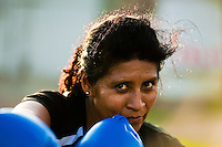 A Peruvian woman practices punching while training in the outdoor boxing school at the Telmo Carbajo stadium in Callao, Peru, 4 April 2013.