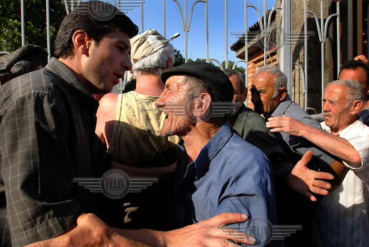 An aid worker (left) tries to calm a crowd of Gori residents, who refused to leave during the Russian occupation of their town, queueing for emergency food aid near the town centre.