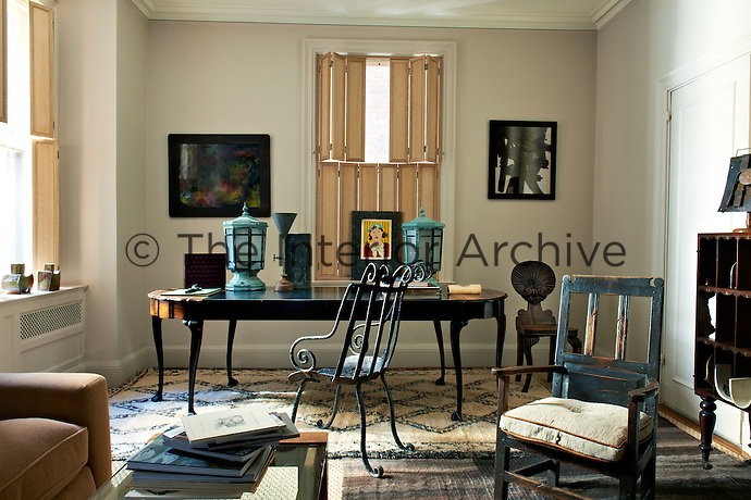 A large antique wooden desk with a sculptural metal chair in front of the shuttered windows of the study