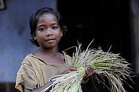 INDIA, Jharkhand, Chaibasa, Adivasi, Ho tribe, girl with rice / INDIEN, Jharkhand , Chaibasa , Dorf Ulijari  , Ho Ureinwohner, Maedchen mit Reis
