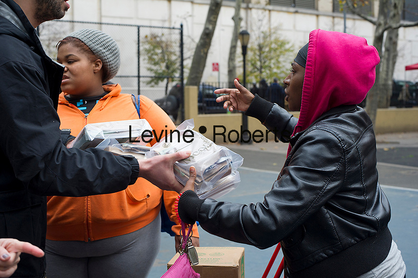 Ready to eat meals and bottled water are distributed  to people in the Chelsea neighborhood in New York where there is no electric power due to Hurricane Sandy  on Friday, November 2, 2012.  (© Frances M. Roberts)