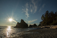 The sun sits low in the sky at Ruby Beach, just north of Kalaloch in Olympic National Park, Washington on July 20, 2016. In the distance are sea stacks, rock formations that are remnants of former headlands that the winds and waters of the Pacific Ocean have since eroded into stacks of rock standing at the beach.