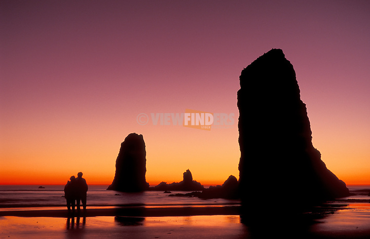 Haystack Rock & sea stacks at sunset with couple on beach; Cannon Beach, Oregon coast.