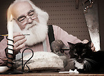Santa Claus painting a toy with his cat