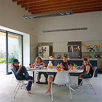 The five daughters of the house enjoy tea at the Eames table in the ground-floor kitchen