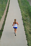 Young Caucasian woman running on a concrete bike path in Boulder, Colorado, USA .  John offers private photo tours in Denver, Boulder and throughout Colorado. Year-round Colorado photo tours.