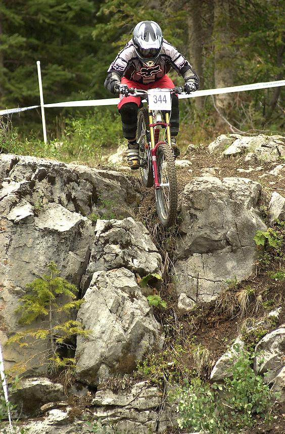 Downhill mountian bike racer Brian Ballard drops a cliff in a mountain bike race at Durango Mountain Resort in Durango, Colorado in 2003.