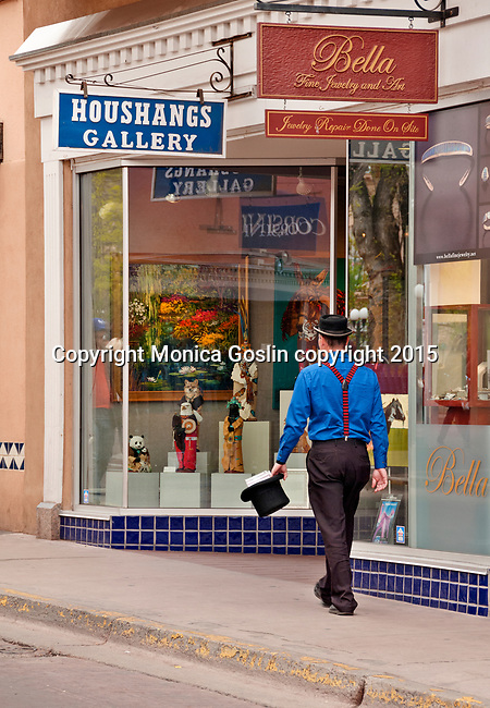 A man wearing a hat and carrying a top hat, walks by galleries on W San Francisco Street downtown