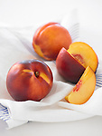 Three nectarines on kitchen towel, one sliced