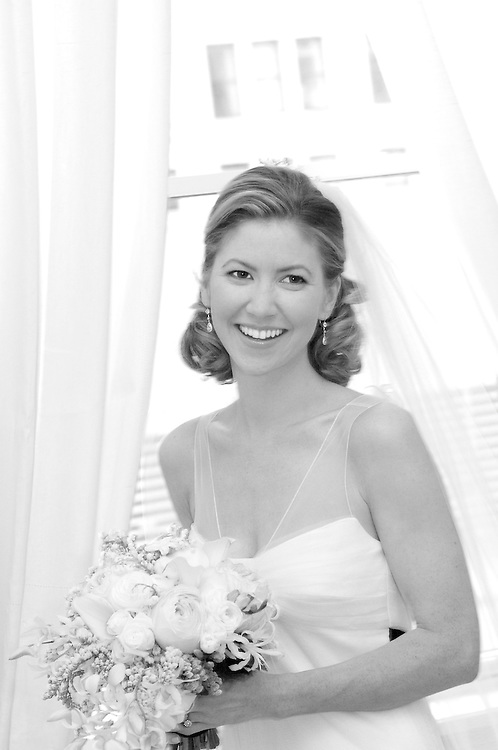 Black & white portrait of bride in front of window.