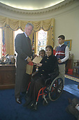 Im this photo released by the White House, United States President Bill Clinton presents Multiple Sclerosis Mother of the Year award to Jill Manning-Fitzgerald, from Doniphan, Nebraska in the Oval Office of the White House in Washington, DC on December 18, 1999.  From left to right: President Clinton; son, Stephen, age 13; Jill Manning-Fitzgerald; daughter, Natalie, age 8.<br /> Mandatory Credit: Sharon Farmer / White House via CNP