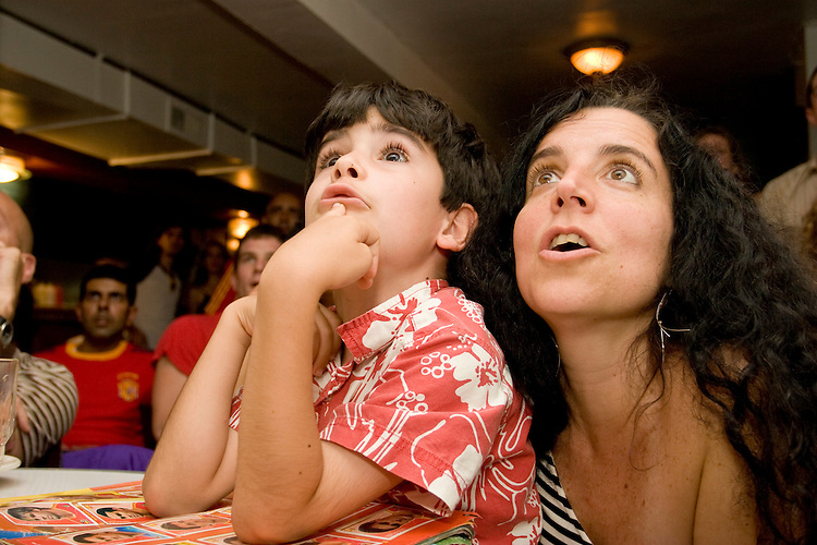 Spain fans Cynthia Vich and her son Sergio Montano cheer on their team during a World Cup match against Tunisia on June 19, 2006 at La Nacional, a restaurant in New York City.<br /> <br /> The World Cup, held every four years in different locales, is the world's pre-eminent sports tournament in the world's most popular sport, soccer (or football, as most of the world calls it).  Qualification for the World Cup is open to any country with a national team accredited by FIFA, world soccer's governing body. The first World Cup, organized by FIFA in response to the popularity of the first Olympic Games' soccer tournaments, was held in 1930 in Uruguay and was participated in by 13 nations.    <br /> <br /> As of 2010 there are 208 such teams.  The final field of the World Cup is narrowed down to 32 national teams in the three years preceding the tournament, with each region of the world allotted a specific number of spots.  <br /> <br /> The World Cup is the most widely regularly watched event in the world, with soccer teams being a source of national pride.  In most nations, the whole country is at a standstill when their team is playing in the tournament, everyone's eyes glued to their televisions or their ears to the radio, to see if their team will prevail.  While the United States in general is a conspicuous exception to the grip of World Cup fever there is one city that is a rather large exception to that rule.  In New York City, the most diverse city in a nation of immigrants, the melting pot that is America is on full display as fans of all nations gather in all possible venues to watch their teams and celebrate where they have come from.
