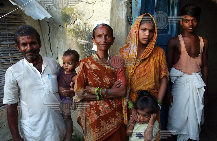 Malachia Devi (centre), who was accused of being a witch by her neighbours and almost beaten to death. She was saved by a local NGO, and lay in a coma for five days. Her husband Ram Lakanshah (left) hid under the stairs when she was taken from the house.