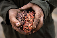 Man holds copper wiring that he extracted from two vacuum cleaner motors in the Cesmin Lug IDP camp in northern Mitrovica. When enough copper is colleted it is sold to a middle man outside the camps.