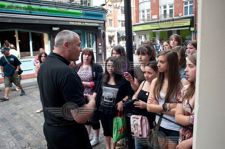 A security guard speaks to Nick Jonas fans waiting outside the Queens Theatre in London where he is appearing as Marius in Les Miserables.