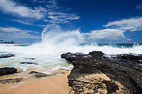 Large waves crash onto lava rocks at Sandy Beach, O'ahu; surfers catch waves in the distance.