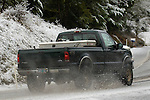 Ford pickup driving on a snowy road