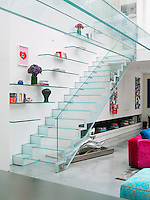 The glass staircase leads up to the mezzanine floor from which a glass bridge then accesses the bedroom