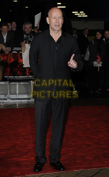 BRUCE WILLIS  .Attending the UK Film Premiere of 'Red' at the Royal Festival Hall, London, England, UK..October 19th 2010.full length suit black hand in pocket finger .CAP/CAN.©Can Nguyen/Capital Pictures.