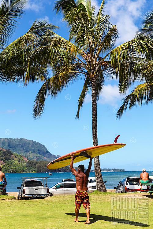 A local surfer carries a surfboard through Black Pot Beach Park, Hanalei, Kaua'i.