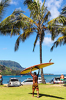 A local surfer carries a surfboard through Black Pot Beach Park, Hanalei, Kaua'i.