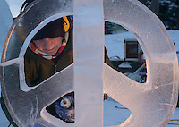 """Tom Lewando works on his sculpture """"Peace On Earth"""" on the final morning of the 2016 Crystal Gallery of Ice Ice Carving Competition in town square."""