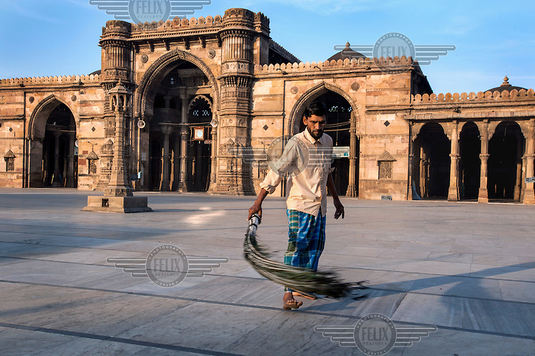 A man sweeps the courtyard of the Jama Masjid in Ahmedabad with a brush made of peacock feathers. Sultan Ahmed Shah, ruler of the Gujarat Sultanate who gave his name to the city of Ahmedabad, completed the mosque in 1424.