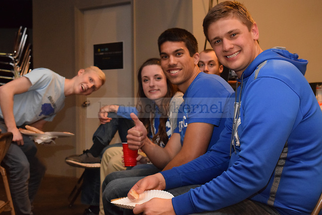 From left to right: junior business major Andrew Boyechko, senior computer engineering major Jeremy Bailey, sophomore nursing major Hannah Johnson, and Luke Warlord eat together during the CSF watch party for the Elite Eight game between UK and Notre Dame on Saturday, March 28, 2015 in Lexington, Ky. Photo by Hunter Mitchell | Staff