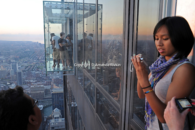 """Visitors are seen on the newly opened glass balconies """"The Ledge"""" at the Skydeck at the Sears Tower in Chicago, Illinois on July 6, 2009."""