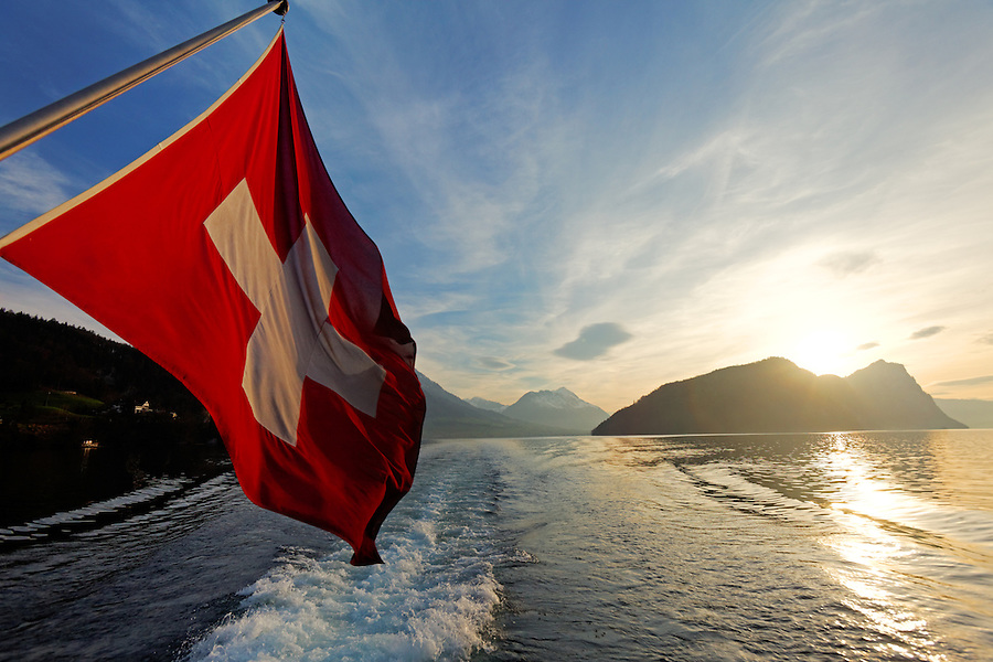 Swiss flag on tour boat cruising Lake Lucerne as sun sets over the Alp mountains, Switzerland