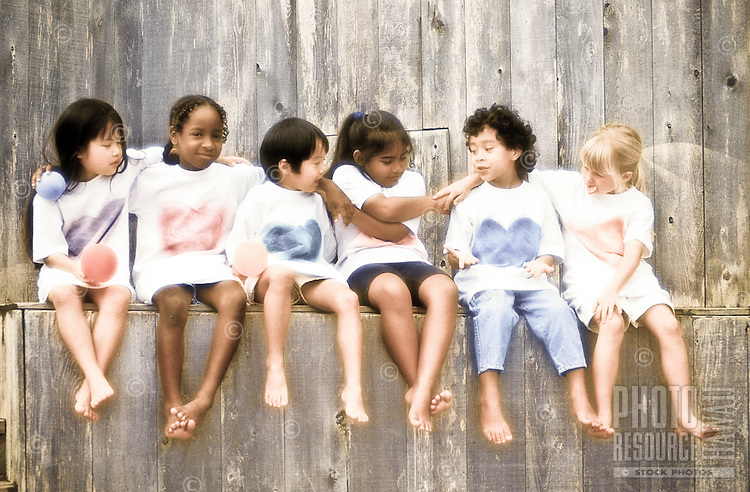 Ethnic mix of children sitting on a wall in Oahu