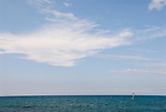 Tiny sailboat on blue ocean waters