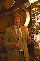 Young Mr Deicas, son of Q Fernando Deicas, president and owner, in the barrel aging cellar holding a bottle of Licor de Tannat 2003, his own creation, a sweet red wine made similar to port wine by adding alcohol to the partially fermented must. Bodega Juanico Familia Deicas Winery, Juanico, Canelones, Uruguay, South America