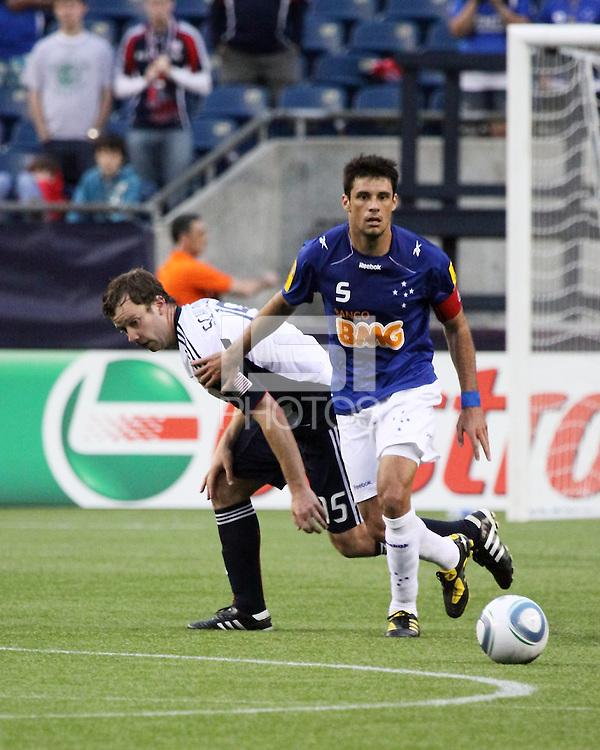 Cruzeiro midfielder Fabricio beats New England Revolution forward Zack Schilawski (15) to the ball.  Brazil's Cruzeiro beat the New England Revolution, 3-0 in a friendly match at Gillette Stadium on June 13, 2010
