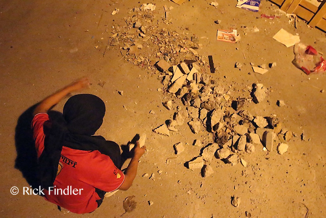 Photographer: Rick Findler..21.04.13 A protester prepares ammunition to throw at the police on the front lines of a clash between riot-police and protesters in Ma'ameer, Bahrain. The number of protests in Bahrain increase dramatically during the sporting event to help bring attention to the ruling bahraini Sunni royal family's many human rights abuses and repression of the country's Shiite people.
