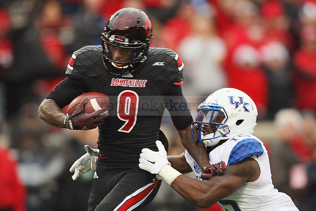 Devante Parker of the Louisville Cardinals stiff arms safety Marcus McWilson on his way to a touchdown during the second half of the game against the Kentucky Wildcats at Papa Johns Cardinals Stadium on Saturday, November 29, 2014 in Louisville, Ky. Louisville defeated Kentucky 44-40. Photo by Michael Reaves | Staff