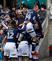 Jed Wallace leaps on the shoulders of his team mates after Shaun Williams of Millwall (right) scores the opening goal in the first minute during the Sky Bet Championship match between Millwall and Nottingham Forest at The Den, London, England on 30 March 2018. Photo by Alan  Stanford / PRiME Media Images.