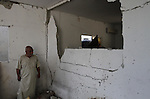 A Palestinian man inspects the damage to his wall after his house was searched by Israeli forces on June 17, 2014 at the Balata refugee camp, close to the northern West Bank city of Nablus. Large numbers of Israeli soldiers raided the northern West Bank city of Nablus and its surroundings early 17 June 2014 in the search of three teenagers, three teenagers - Eyal Yifrah, 19, Gilad Shaar, 16, and Naftali Frenkel, 16 - missing since 08 JUne 2014, near the Gush Etzion settlement bloc, north of Hebron. Photo by Nedal Eshtayah
