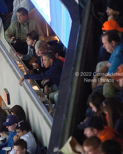 United States President Barack Obama (with arm over rail) watches the Syracuse vs. Marquette East Regional Final basketball game at the Verizon Center in Washington, Saturday, March 30, 2013..Credit: Martin Simon / Pool via CNP