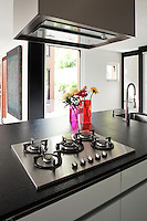 The central kitchen island has a thick black granite worktop