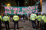 Police stand outside the boundary of the climate camp. The Climate Camp in the City was set up  in front of the European Climate Exchange during the G20 meetings in 2009. The aim of the camp was to protest against the proposed carbon trading schemes that many feel will not solve the climate crisis, while generating windfall profits for traders. The camp maintained a policy of non-violence, despite police actions to the contrary. The protestors were forcefully evicted from the site late in the evening after the mainstream media had left.  The protests at the G20 have sparked investigations into policing policies in the UK. (©Robert vanWaarden)