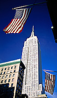 USA, New York, New York City. Empire State Building with USA flags