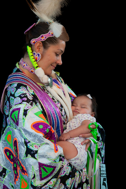 Traditionally dressed in colorful fancy shawl regalia is a Mother tenderly holds her infant daughter in her arms, Karen and Cassie Osborne (Shoshone-Bannock)