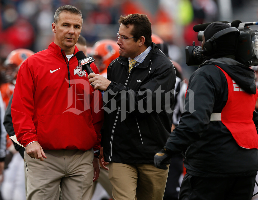 Ohio State Buckeyes head coach Urban Meyer is interviewed by ESPN while leaving the field for halftime during Saturday's NCAA Division I football game against Illinois at Memorial Stadium in Champaign, Il., on November 16, 2013. (Barbara J. Perenic/The Columbus Dispatch)