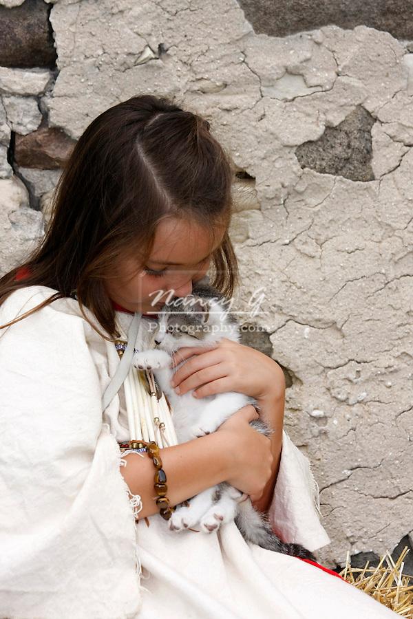 A Native American Indian girl hugging a kitten