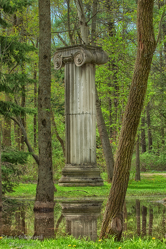 A column stands alone in the woods on the grounds of The Guild in Toronto.
