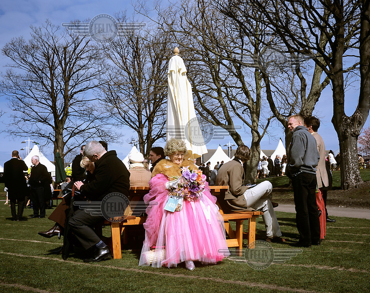 An elderly lady in a pink dress and tiara sits among spectators on Lady's Day during The Grand National horse races at Aintree racecourse. ..