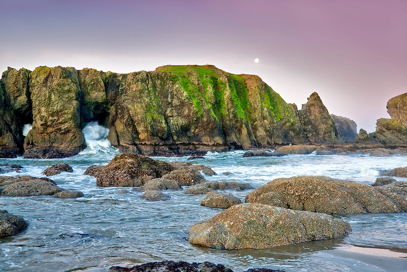 Rocks, moon, low tide and wave at Bandon beach. Oregon
