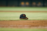 An AZL Giants hat and glove rests on the field between innings of the game against the AZL Athletics on August 5, 2017 at Scottsdale Stadium in Scottsdale, Arizona. AZL Athletics defeated the AZL Giants 2-1. (Zachary Lucy/Four Seam Images)
